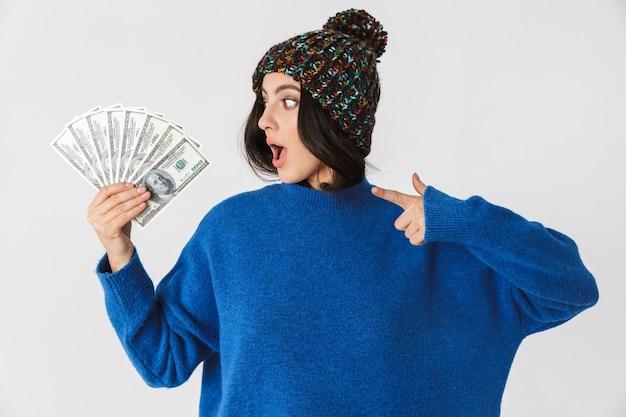 Porträt der erfreuten frau, die wintermütze hält, die fan des dollargeldes im stehen hält, lokalisiert auf weiß