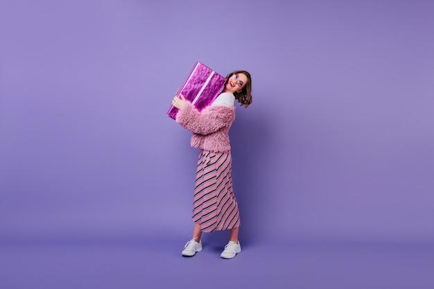 Porträt der erfreuten kaukasischen frau in den turnschuhen, die geschenkbox halten. innenaufnahme des eleganten weiblichen modells, das mit geburtstagsgeschenk aufwirft und lächelt.