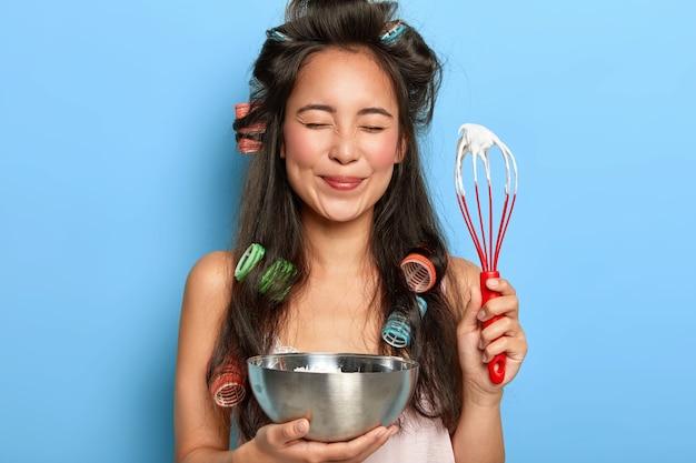 Porträt der erfreuten schönen koreanischen dame hält schläger und schüssel, macht süße sahne für kekskuchen, trägt lockenwickler