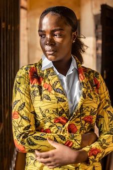 Porträt der ernsten afrikanischen frau im blumenmantel