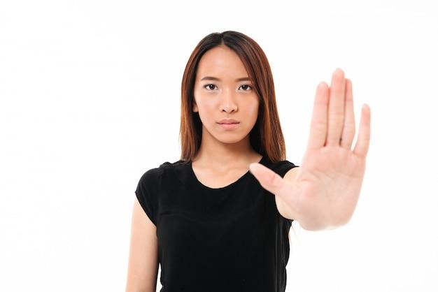 Porträt der ernsten asiatischen frau, die mit ausgestreckter hand steht und stoppgeste zeigt
