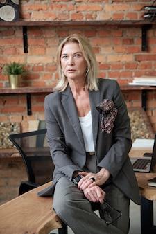 Porträt der ernsten dame der exekutive mit brille in der hand, die auf tisch im eigenen büro sitzt