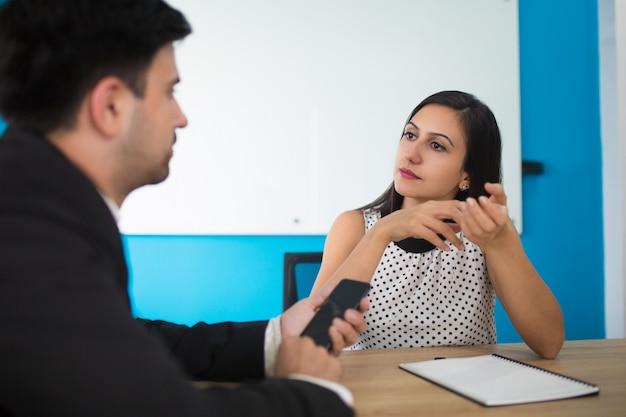 Porträt der ernsten jungen geschäftsfrau, die auf partner hört