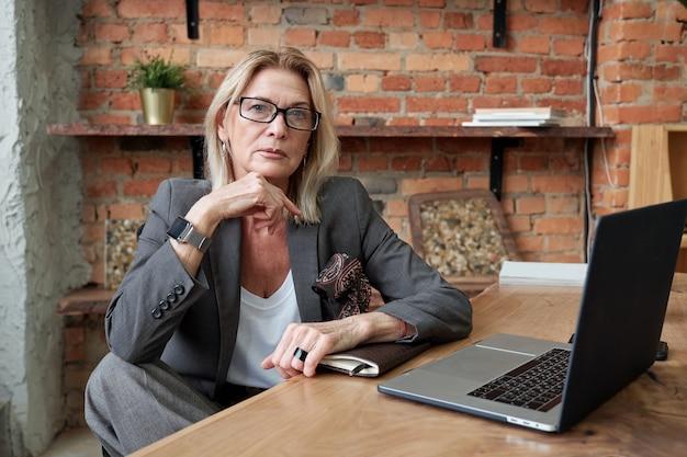 Porträt der ernsten modischen reifen geschäftsdame in der jacke, die am schreibtisch mit offenem laptop im eigenen büro sitzt