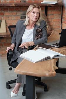 Porträt der ernsthaften strengen reifen chefin in der jacke mit schal in der tasche, die am holztisch mit hauptbuch sitzt