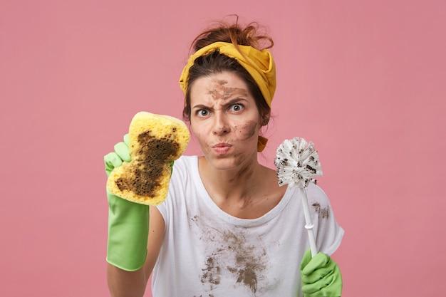 Porträt der erschwerten frau mit schmutzigem gesicht, das gelbes stirnband und weißes t-shirt hält, das schwamm und abstergent hält, das über rosa wand aufwirft. müde gereizte unordentliche frau, die hausarbeit macht