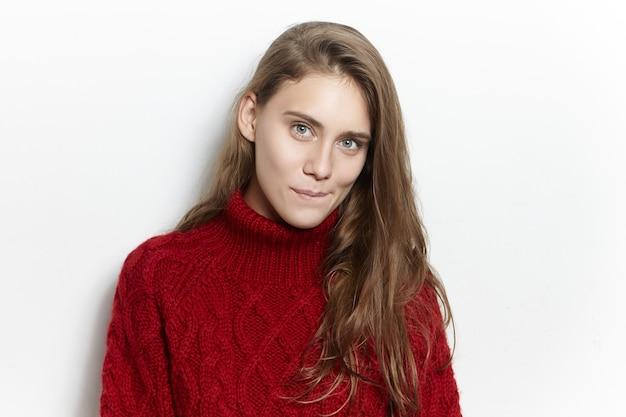 Porträt der erstaunlichen herrlichen jungen europäischen frau mit der langen losen frisur, die isoliert im kuscheligen marsala-pullover posiert und mit mysteriösem neugierigem gesichtsausdruck starrt, lippen beißend