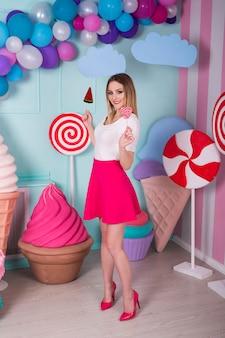 Porträt der erstaunlichen süßen zahnfrau im rosa kleid, das süßigkeiten hält und mit riesigem eis aufwirft. lutscher wassermelone