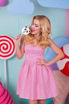 Porträt der erstaunlichen süßen zahnfrau im rosa kleid, das süßigkeiten hält und mit riesigem eis aufwirft. lutscherpanda
