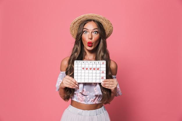 Porträt der erstaunten frau, die strohhut hält zykluskalender hält