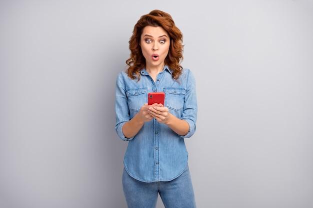 Porträt der erstaunten frau verwenden smartphone lesen soziale netzwerk neuheit beeindruckt schreien unglaublich unerwartet tragen gut aussehen outfit isoliert über graue farbe wand