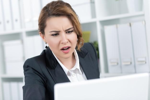 Porträt der erstaunten jungen geschäftsfrau, die laptop-monitor aufmerksam betrachtet