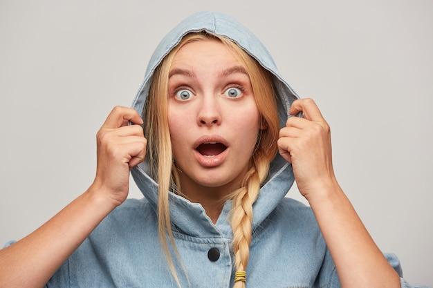 Porträt der erstaunten schönen blonden jungen frau mit zopf, hände halten kapuze, sieht mit offenen augen aus