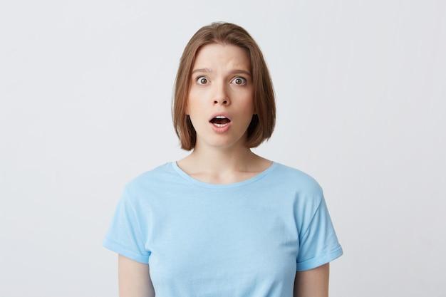 Porträt der erstaunten schönen jungen frau im blauen t-shirt, das mit geöffnetem mund steht und sich schockiert fühlt