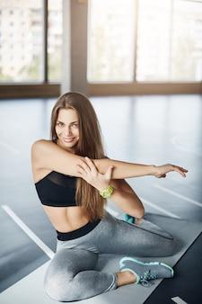 Porträt der erwachsenen fitnesstrainerin, die ihre arme ausdehnt, die sich vor einer eintägigen übungsarbeit aufwärmen