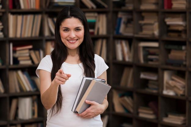 Porträt der erwachsenen frau, die bücher an der bibliothek hält