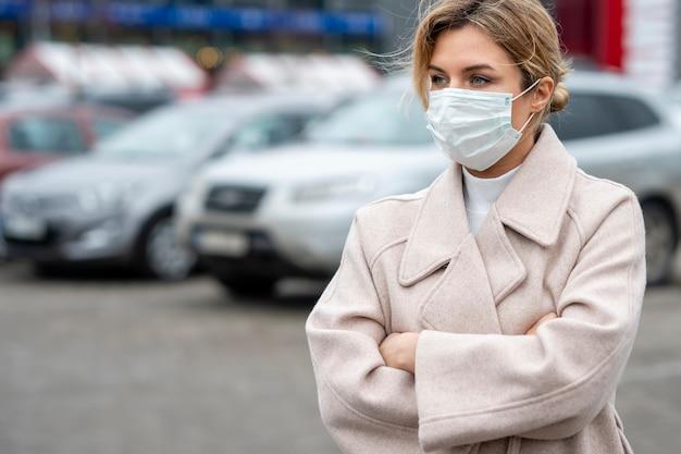 Porträt der erwachsenen frau, die chirurgische maske trägt