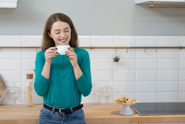 Porträt der erwachsenen frau, die eine tasse kaffee genießt