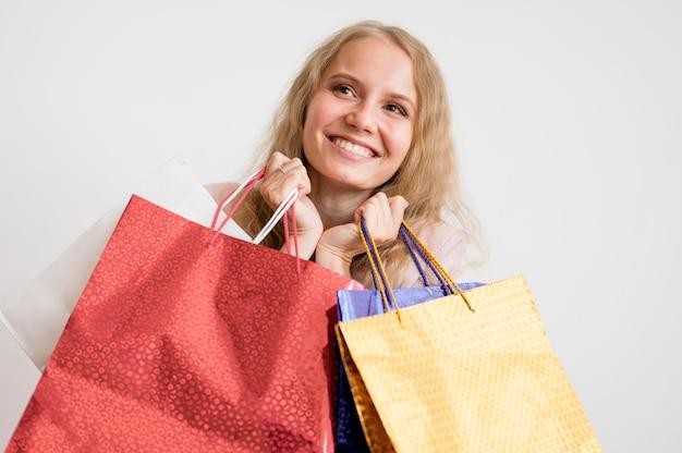 Porträt der erwachsenen frau, die einkaufstaschen hält