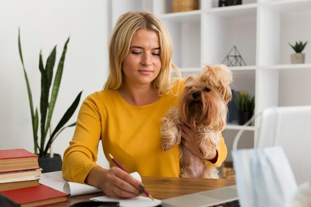 Porträt der erwachsenen frau, die hund während der arbeit hält