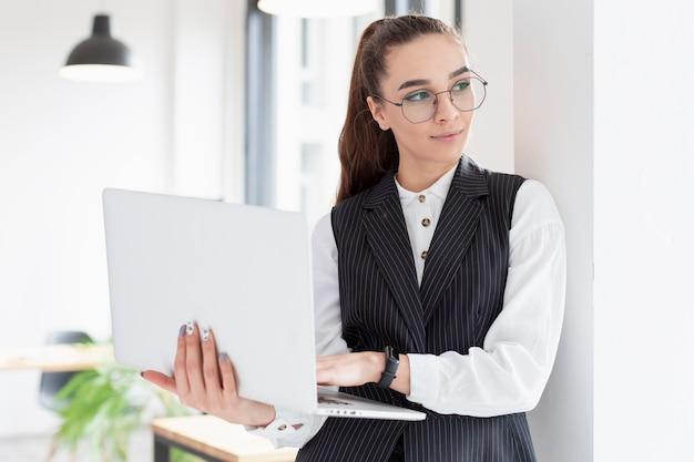 Porträt der erwachsenen frau, die laptop hält