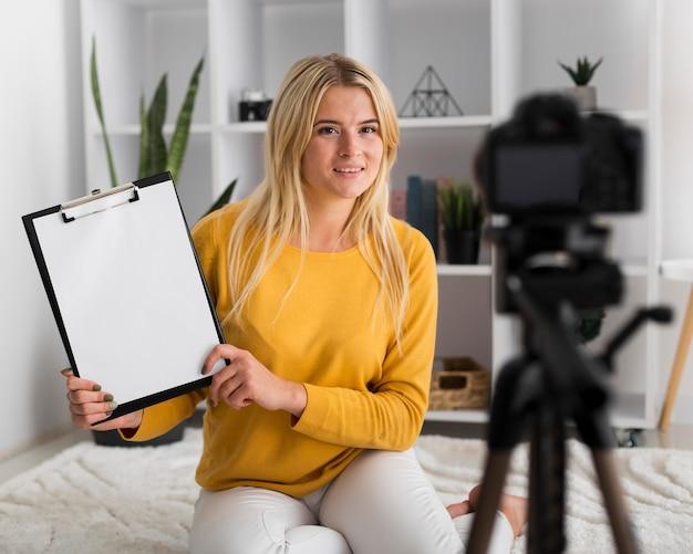 Porträt der erwachsenen frau, die video zu hause aufzeichnet