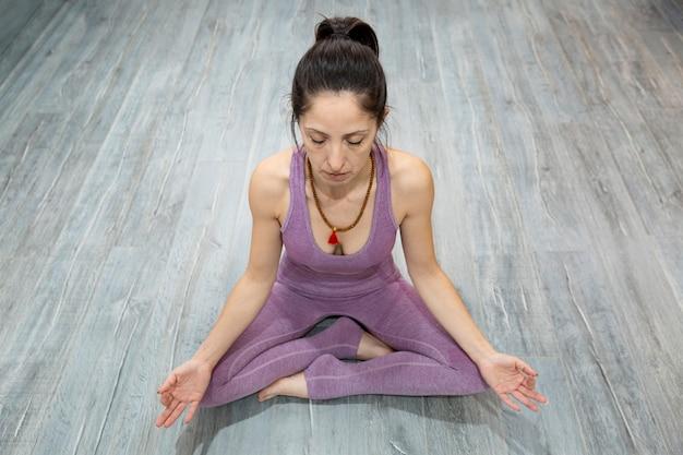 Porträt der erwachsenen frau, die yoga in der meditationshaltung praktiziert. sie sitzt auf einem holzboden. platz für text.
