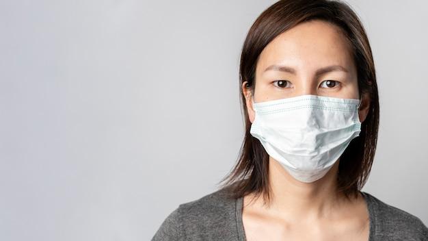 Porträt der erwachsenen frau mit der chirurgischen maske