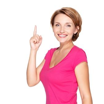 Porträt der erwachsenen glücklichen frau, die mit ihrem finger über weiße wand zeigt