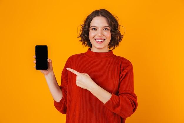 Porträt der europäischen frau 20s, die pullover hält, der smartphone hält und demonstriert, während lokalisiert über gelb steht