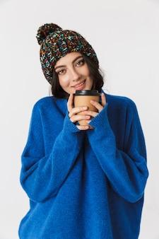 Porträt der europäischen frau, die wintermütze trägt, die lächelt und kaffee zum mitnehmen trinkt, während sie steht, lokalisiert auf weiß