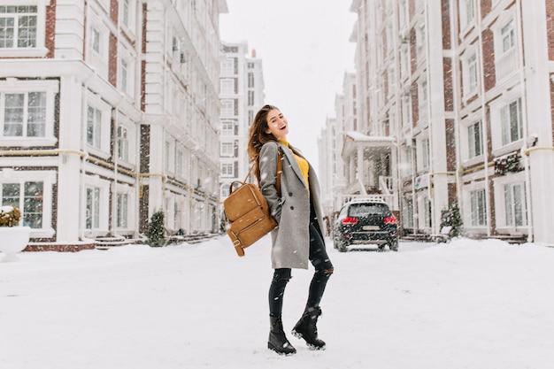 Porträt der europäischen frau in voller länge trägt eleganten mantel bei schneebedecktem wetter. fröhliche junge frau mit stilvollem rucksack, der auf hauptstadtstraße im wintertag steht.