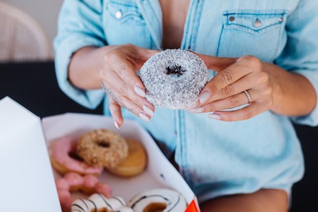 Porträt der europäischen frau mit blondem haar, das donuts in der küche zu hause villa genießt.