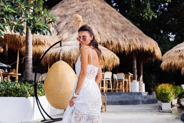 Porträt der europäischen romantischen frau im weißen sommerkleid außerhalb des hotelresorts im eierstrohstuhl.