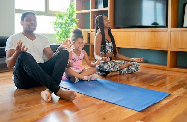 Porträt der familie, die yoga-übung macht, während sie zu hause bleibt. sportkonzept