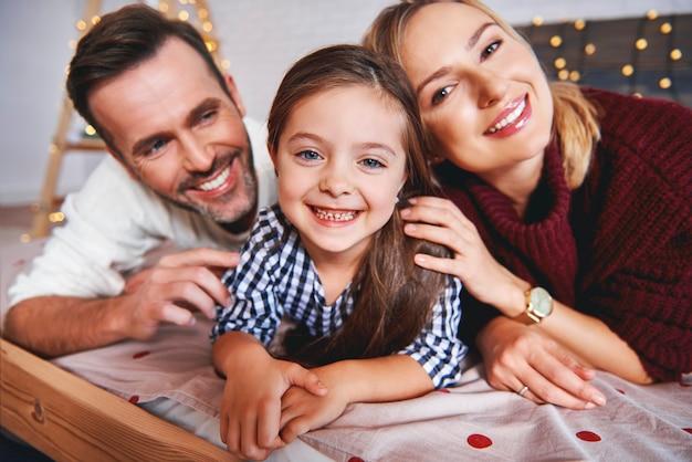 Porträt der familie, die zur weihnachtszeit im bett liegt