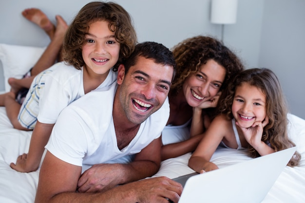 Porträt der familie, die zusammen laptop auf bett verwendet