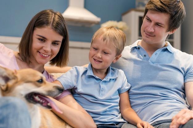 Porträt der familie, die zusammen mit hund spielt
