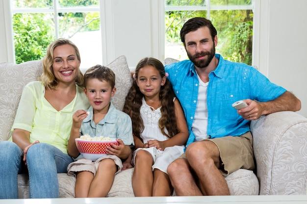 Porträt der familie fernsehend beim sitzen auf sofa