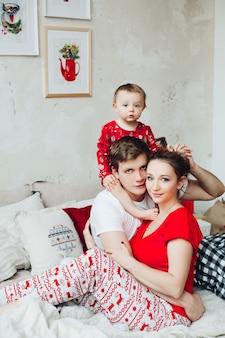 Porträt der familie in den pyjamas, die zusammen im bett in verziertem schlafzimmer für weihnachten und die umfassung sitzen.