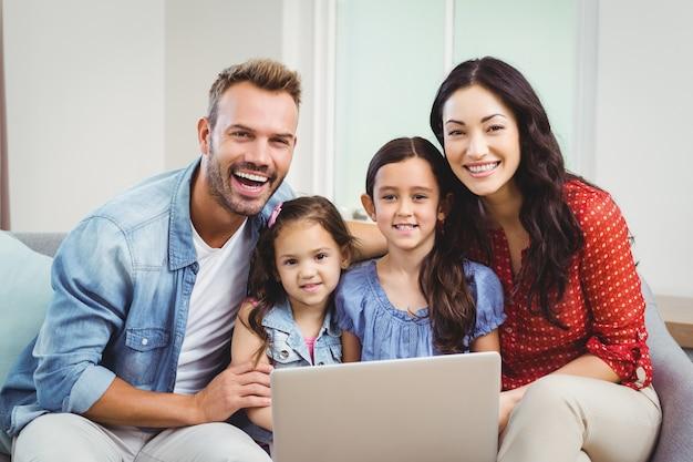 Porträt der familie lächelnd und laptop auf sofa verwendend