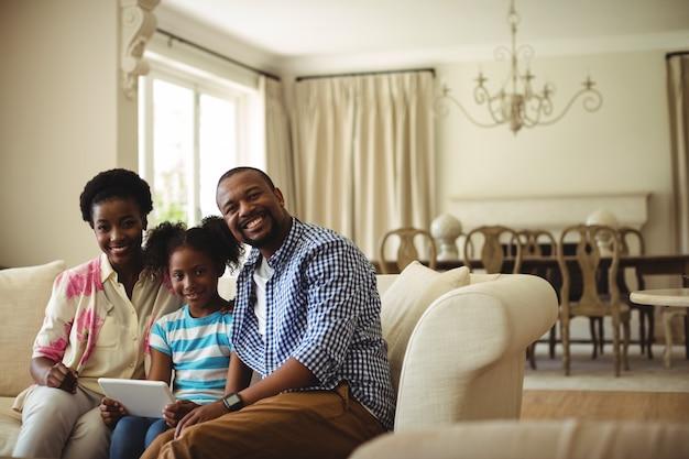Porträt der familie mit digitaler tablette im wohnzimmer