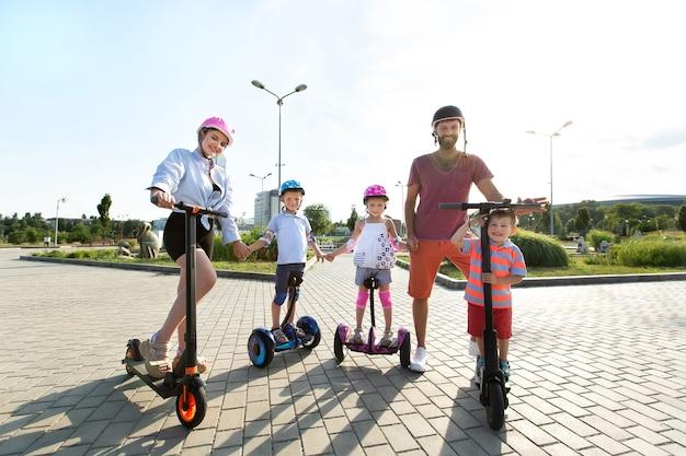 Porträt der familie mit kindern auf elektrorollern und kreiselrollern im park im sommer.