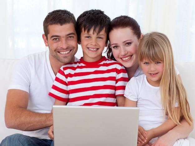 Porträt der familie zu hause unter verwendung eines laptops