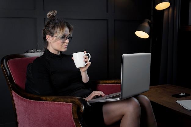 Porträt der firmengeschäftsfrau, die am laptop arbeitet