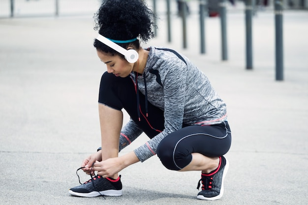 Porträt der fitten und sportlichen jungen frau, die ihre schnürsenkel vor einem lauf binden.