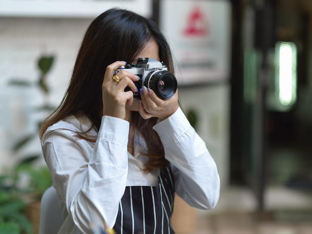 Porträt der fotografin, die foto mit digitalkamera im café nimmt
