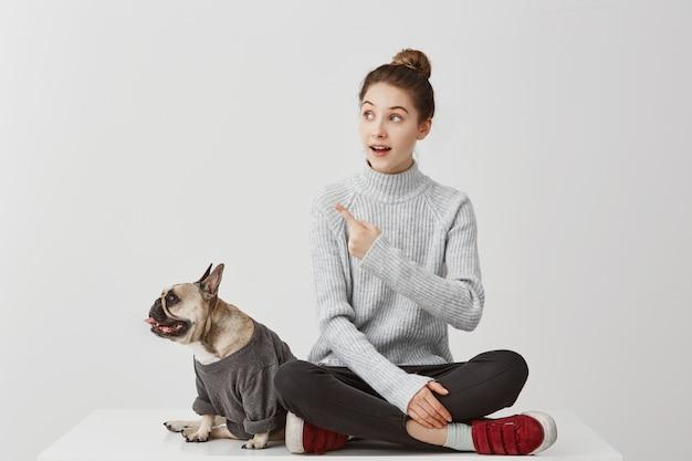 Porträt der französischen bulldogge, gekleidet im sweatshirt, das auf etwas beiseite schaut, während hübsches mädchen gestikuliert. fotografin, die auf merkwürdige sache achtet. menschen, tierkonzept