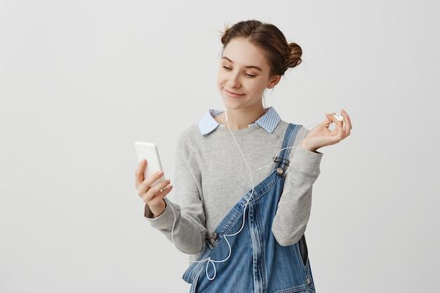 Porträt der frau 20s, die auf bildschirm des handys mit angenehmem breitem lächeln schaut. charmanter weiblicher teenager, der selfie-porträt macht, während musik draußen hört. interaktionskonzept