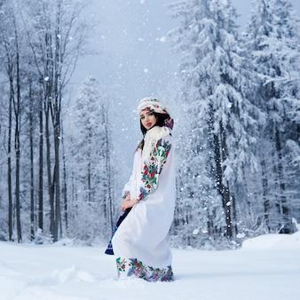 Porträt der frau am wintertag auf verschneitem landschaftshintergrund
